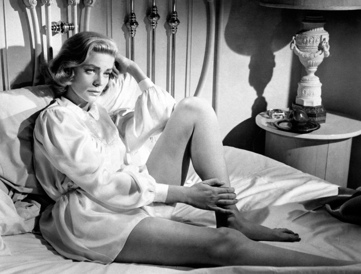 Lauren Bacall seated on a bed